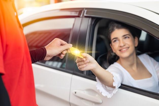 Felice donna conducente cliente che dà il pagamento con carta di credito al personale per il costo del carburante alla stazione di servizio o il costo del servizio al garage