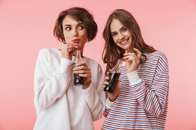 Amici felici delle donne isolate sopra la soda bevente della parete rosa.