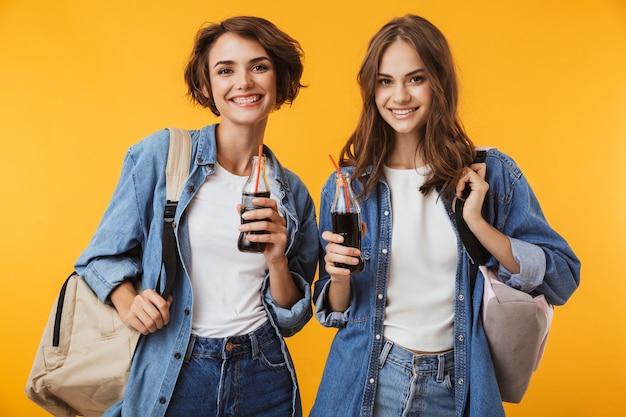 Amici felici delle donne isolate sopra la soda bevente della parete gialla.