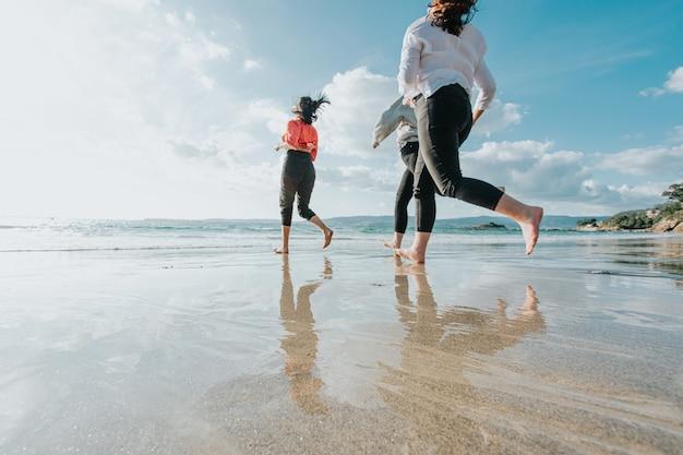 Le amiche felici corrono sulla spiaggia del mare durante una giornata luminosa, gli amici si rilassano felici divertendosi giocando sulla spiaggia vicino al mare quando il tramonto la sera
