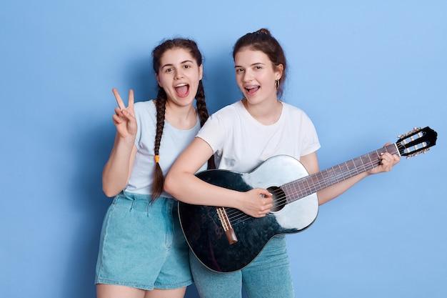 Amici felici delle donne con la chitarra e mostrando il segno di v
