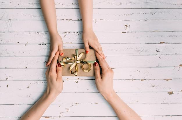 Felice giorno delle donne. il piccolo bambino si congratula con la mamma e le fa un regalo su fondo di legno.