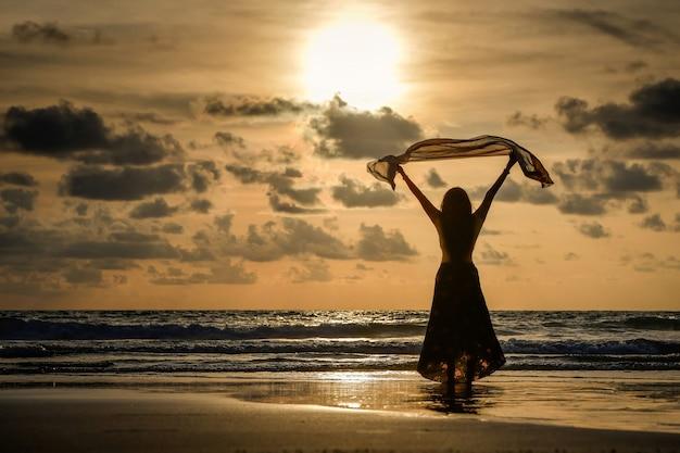 Donne felici state in piedi e ammirate il tramonto sul mare al tramonto, tenendo in mano un panno sottile.