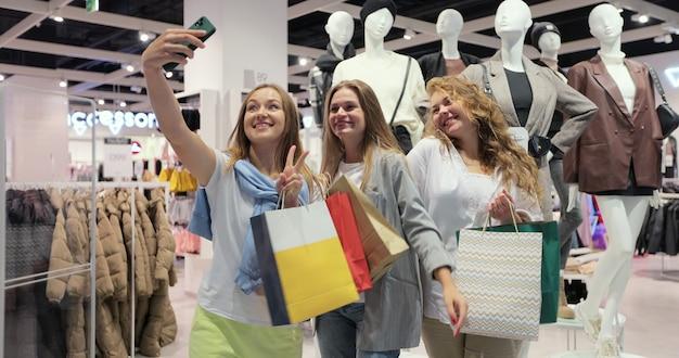 Donne felici che prendono selfie dopo lo shopping. ragazze sorridenti. posano per le foto, si mettono le mani sui capelli, sul viso. avere molte borse della spesa colorate.