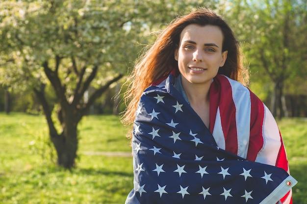 Le donne felici con la bandiera americana usa celebrano il 4 luglio