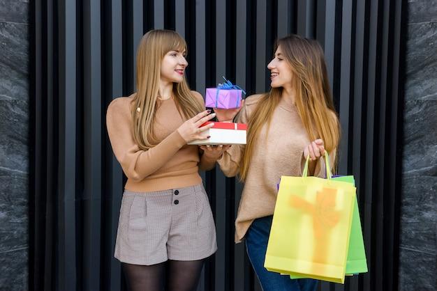 Donne felici con regali e borse della spesa che camminano sulla strada della città. concetto di celebrazione di capodanno e natale