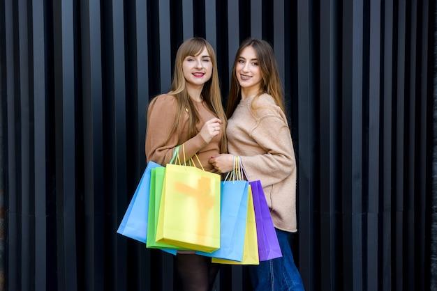 Donne felici con borse della spesa in pellicce in posa sulla strada della città