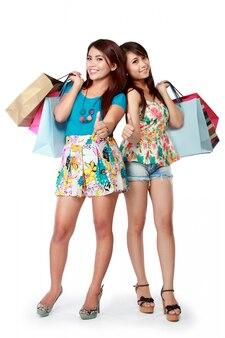 Donne felici con i sacchetti della spesa che mostrano i pollici su