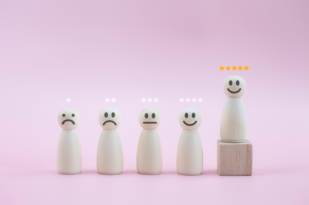 Felice persona in legno modella una faccina a 5 stelle tra le persone su sfondo rosa pastello
