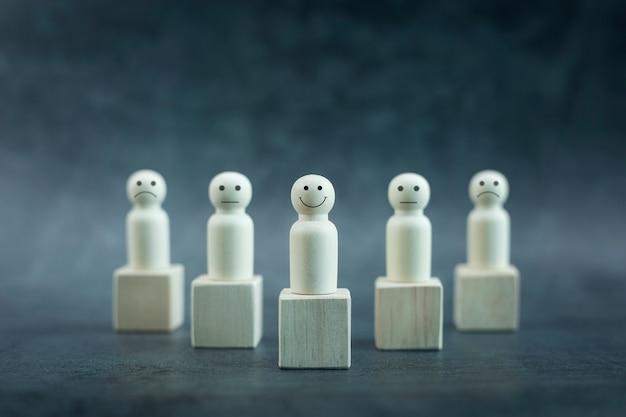 La persona di legno felice modella una faccina tra le persone su sfondo nero