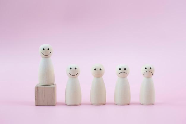 Felice persona in legno modella una faccina tra le persone su sfondo rosa pastello