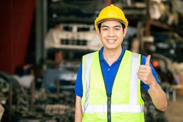 Felice lavoratore uomo asiatico maschio con tuta di sicurezza lavora in fabbrica di ingegneria pollice in alto segno