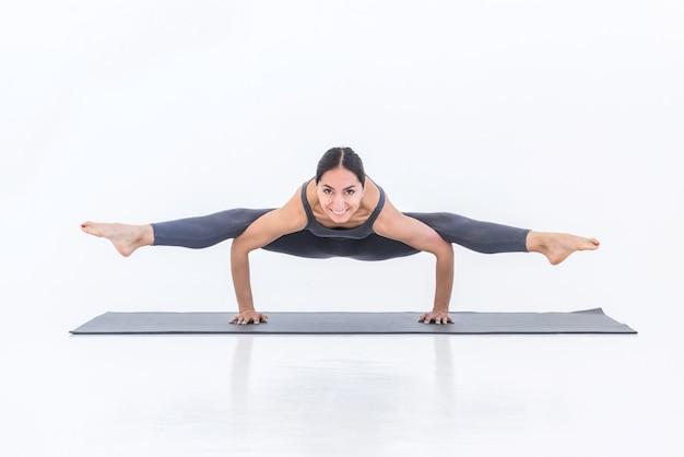 Felice donna yogi che pratica yoga sul tappetino facendo posa di spago in piedi sulle mani