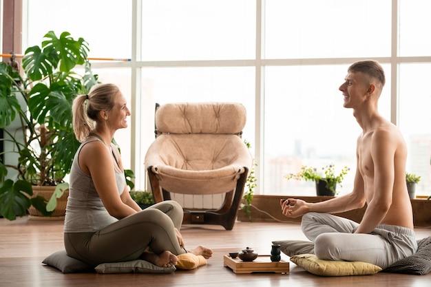 Felice giovane coppia attiva seduti su morbidi cuscini sul pavimento uno di fronte all'altro, rilassarsi, parlare e bere una tisana aromatica