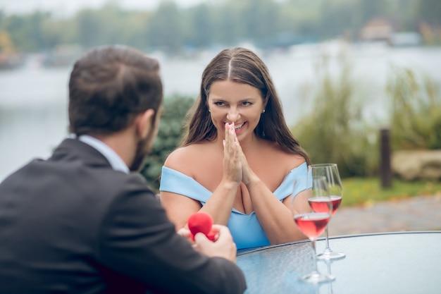 Felice giovane adulto piuttosto emotivo donna e uomo che offre anello nel pomeriggio in caffè estivo