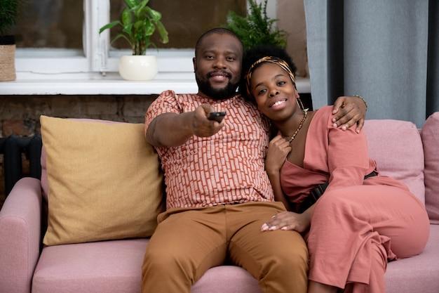 Felice giovane affettuoso marito africano e moglie seduti sul divano contro la finestra in soggiorno e guardando un programma tv o un film