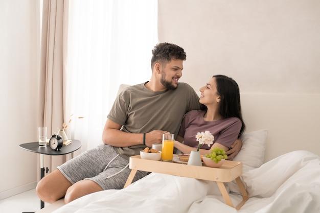 Felice giovane coppia affettuosa che si guarda l'un l'altro con un sorriso mentre è seduta a letto, fa una gustosa colazione e discute di qualcosa di carino
