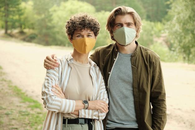 Felice giovane coppia affettuosa in maschere protettive fatte a mano e abbigliamento casual in piedi in un ambiente naturale