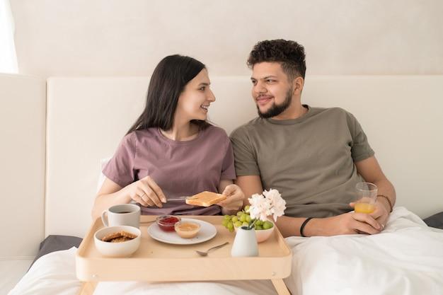 Felice giovane coppia affettuosa in t-shirt seduta a letto e parlando durante la colazione mentre la donna spalma il burro di arachidi sul pane tostato