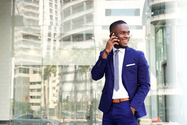 Giovane uomo d'affari afroamericano felice con il telefono cellulare