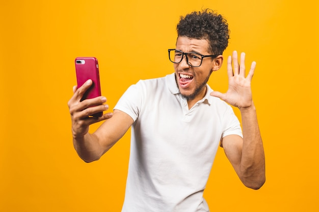 Felice giovane uomo afroamericano prendendo un selfie per telefono.