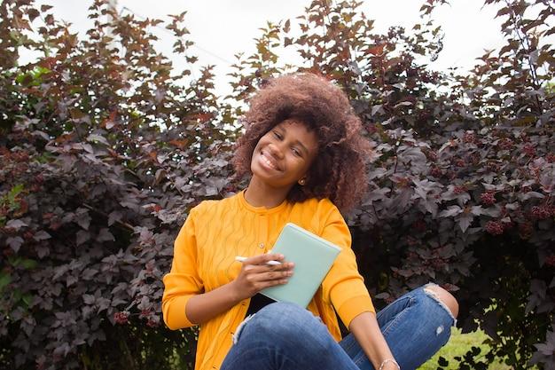 Uno studente afroamericano felice e giovane nel parco