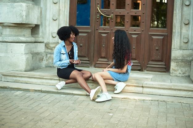 La giovane donna afroamericana felice che sorride gode di una conversazione divertente con un amico indiano, una ragazza adolescente di razza mista parla ridendo all'aperto