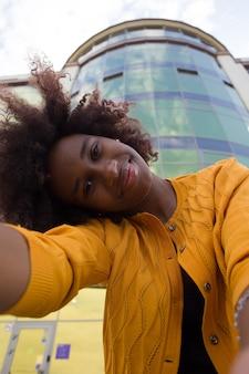 Una donna afroamericana felice e giovane prende un selfie, primo piano