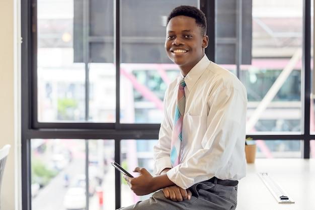 Felice giovane uomo d'affari africano studente utente professionale tenere lo smartphone online sedersi a casa scrivania in ufficio utilizzando la tecnologia del telefono cellulare