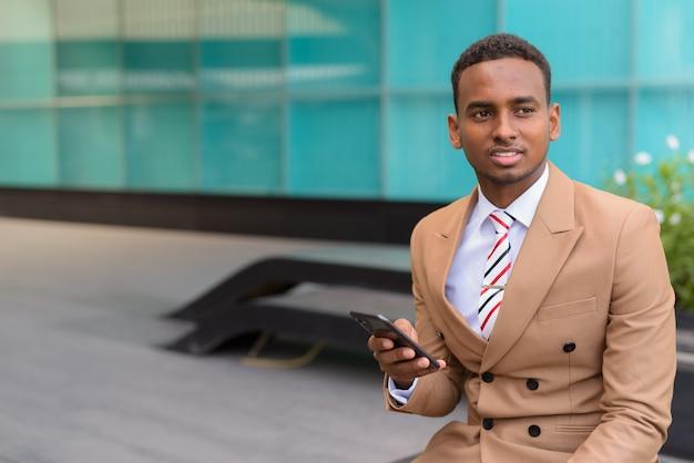 Felice giovane imprenditore africano con il telefono pensando e seduto in città all'aperto