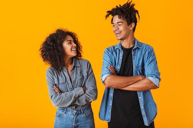 Felice giovane coppia africana che indossa abiti casual in piedi isolato, braccia conserte
