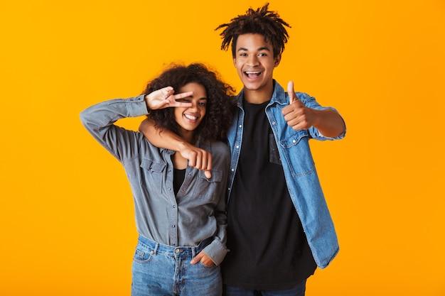 Felice giovane coppia africana che indossa abiti casual in piedi isolato