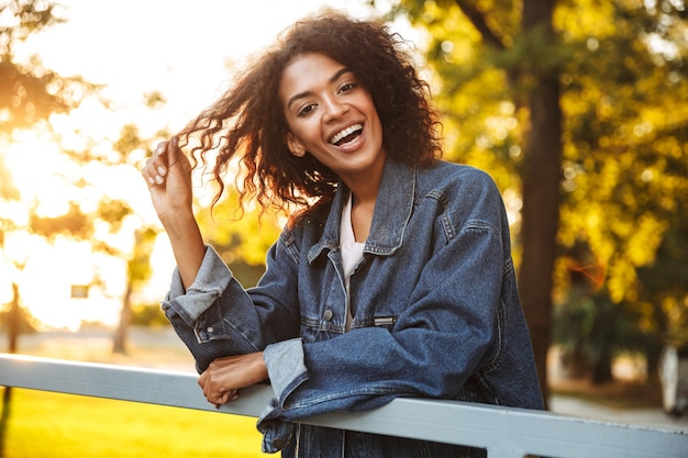 Felice giovane ragazza africana in giacca di jeans
