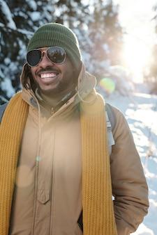 Felice giovane africano in abbigliamento invernale e occhiali da sole