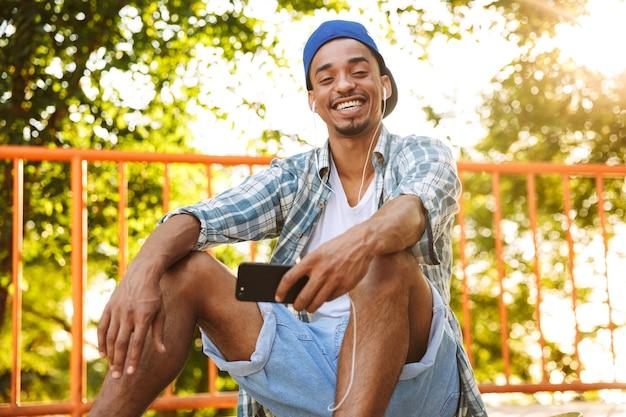 Felice giovane uomo africano in auricolari