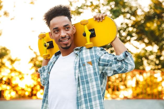 Felice giovane uomo africano con lo skateboard