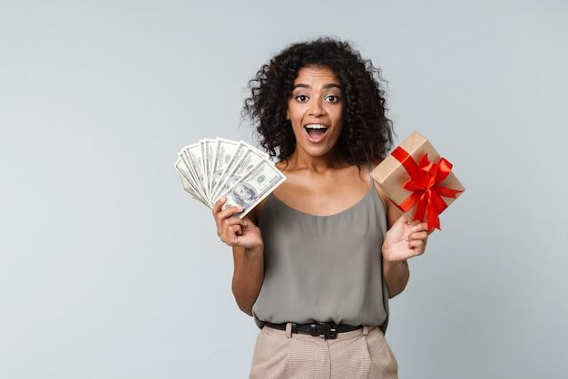 Felice giovane donna africana vestita casualmente in piedi isolato, tenendo in mano una confezione regalo, mostrando banconote di denaro