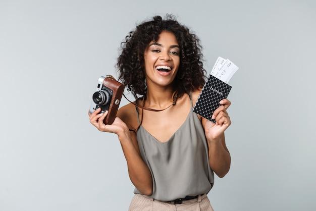 Felice giovane donna africana vestita casualmente in piedi isolato, tenendo la macchina fotografica, mostrando il passaporto con i biglietti aerei