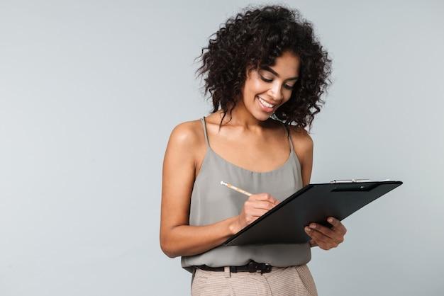 Felice giovane donna africana vestita casualmente in piedi isolato, prendendo appunti in un blocco note