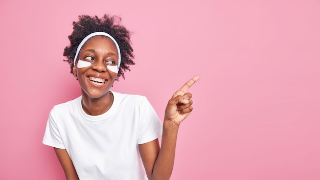 Felice giovane donna afroamericana con i capelli ricci sorride ampiamente mostra denti bianchi perfetti applica cerotti sotto gli occhi