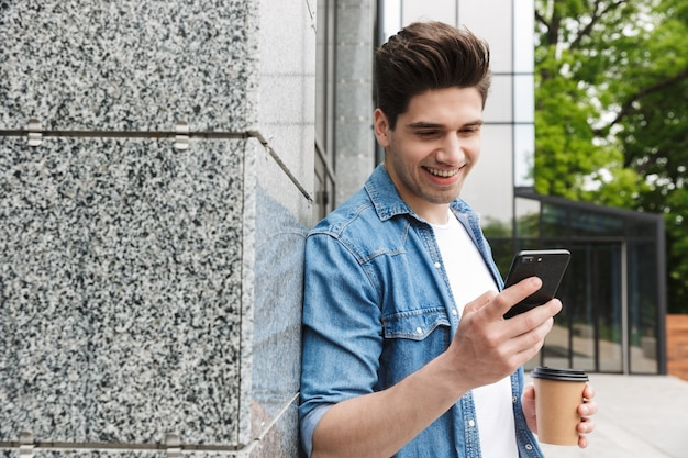Felice giovane uomo d'affari incredibile in posa all'aperto fuori a piedi chiacchierando con il cellulare bevendo caffè.