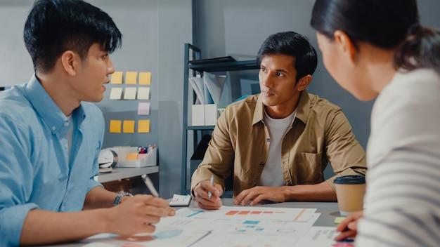 Giovani uomini d'affari e imprenditrice asiatici felici che si incontrano per raccogliere idee nuove sul progetto