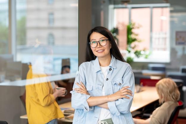 Felice giovane imprenditrice asiatica in giacca di jeans, incrociando le braccia per il petto, mentre in piedi davanti alla telecamera contro l'ufficio