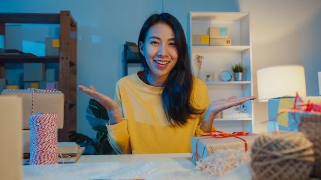 Felice giovane imprenditrice asiatica guardando la vendita anteriore introduce il prodotto al video del cliente