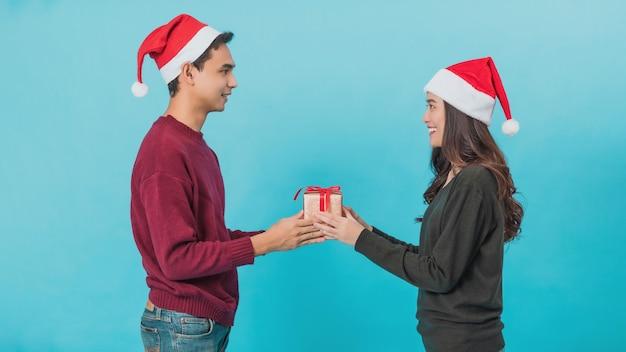 Felice giovane coppia asiatica in possesso di contenitori di regalo di natale con la faccia sorridente felice isolata sul blu