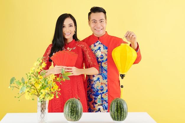 Felice giovane coppia asiatica in piedi a tavola con cocomeri freschi e vaso con rami di albicocca e mostrando lanterna di seta e buste di denaro fortunato