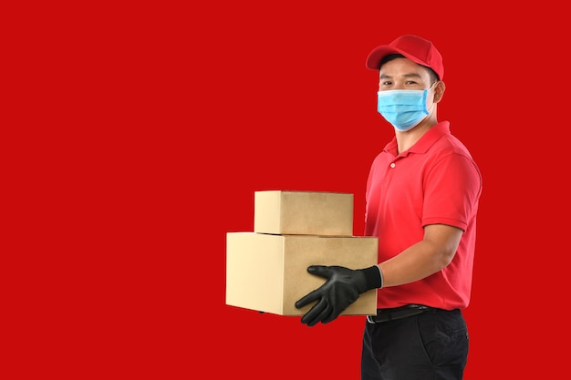 Felice giovane uomo di consegna asiatico in uniforme rossa, maschera medica, guanti protettivi portare scatola di cartone in mani su sfondo rosso. il ragazzo delle consegne dà la spedizione del pacco. durante l'epidemia di covid-19