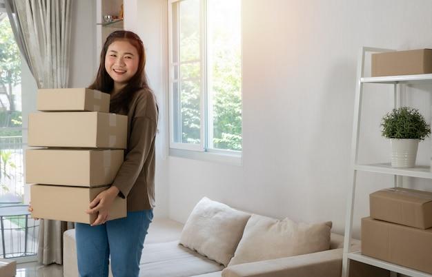 Felice giovane imprenditore asiatico sta organizzando scatole per la consegna ai clienti