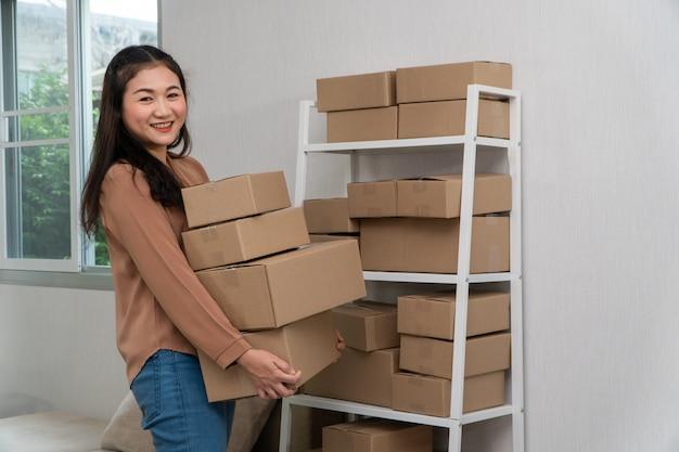 Felici giovani imprenditori asiatici stanno organizzando scatole per la consegna di prodotti ai clienti.