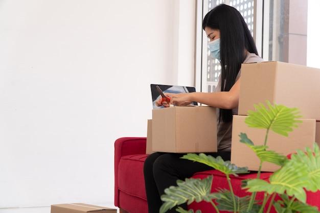 Felici giovani imprenditori asiatici su una maschera stanno imballando scatole per la consegna di prodotti ai clienti